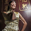 Asichinese girl in cheongsam and teasing — Stock Photo #6663225