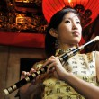 Asian chinese woman holding a flute — Stockfoto