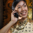 Asian chinese girl in traditional dress with phone - Stock Photo