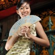 Asian chinese lady with a fan in her hand — Stock Photo