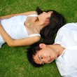 Asian chinese couple lying on the grass with various expressions - Stock Photo