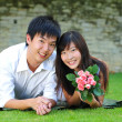 Asian Chinese couple lying on the grass in love — Stock Photo