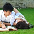 Asian chinese couple reading in the park — Stock Photo