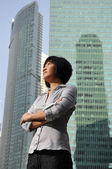 Ambitious young asian woman with buildings in the background — Stock Photo
