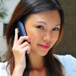 Asian chinese office lady using her mobile communicator - Stock Photo