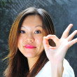 Smiling Asian chinese girl making an ok sign with her hands - Stock Photo