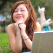 Asian Chinese girl with her laptop outdoors - Stock Photo
