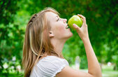 Beautiful girl with the apples on the grass — Stock Photo