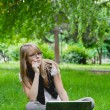 Beautiful girl in the park with laptop — Stock Photo
