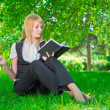 Business woman with notebook on grass — Stock Photo