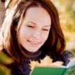 Young woman reading book in autumn — Stock Photo