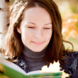 Smiling woman reading book in autumn — Stock Photo