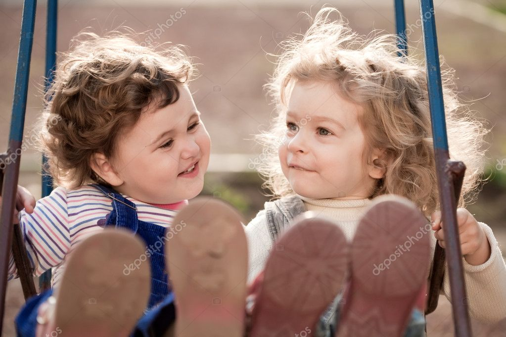 Twin baby sisters playing on swing in autumn park — Stock Photo #6269526