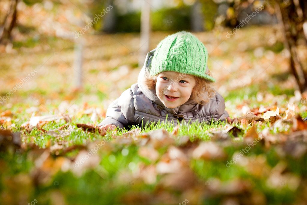 Happy baby girl laying on yellow leaves in autumn park — Stock Photo #6269535
