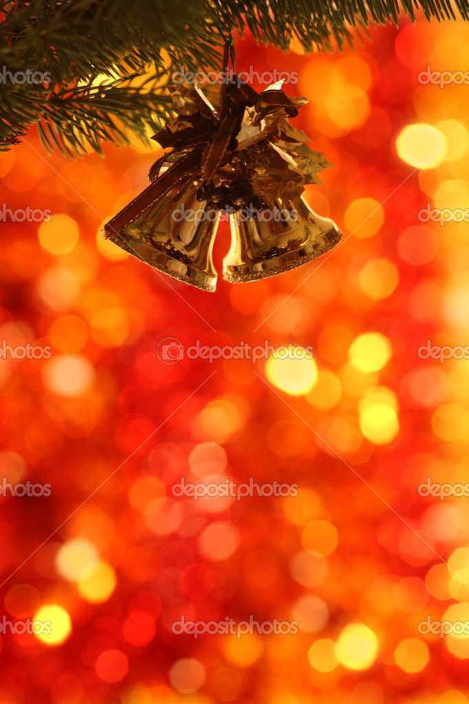 Christmas bells on branch of fir-tree against blurred background — Stock Photo #6270484