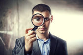 Detective looking through magnifying glass in subway tunnel. Lig — Stock Photo