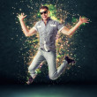 Jumping smiling young man on glowing abstract background — Stock Photo