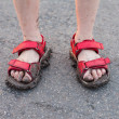 Closeup of child's dirty feet in red sandals on asphalt — Stock Photo #6479170
