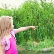 Blonde little girl shows forefingers aside near river with canes — Stock Photo #6479346