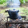 Black old smoked teapot on the campfire on picnic in wood in the — Stock Photo #6479403