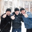 Royalty-Free Stock Photo: Three happy young men showing thumb up in winter