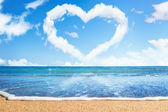 Beach and sea. Heart of clouds on sky. Symbol of love — Stock Photo