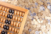 Accounting abacus and heap of coins — Stock Photo