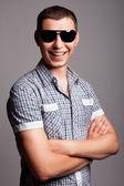 Sonriente joven feliz en gafas de sol — Foto de Stock