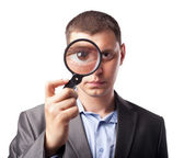 Businessman looking through a magnifying glass — Stock Photo