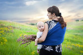 Mother and baby boy in sling on green meadow — Stock Photo