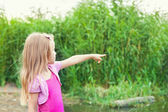 Blonde little girl shows forefingers aside near river with canes — Stock Photo