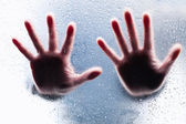 Silhouettes of two right hands behind wet glass — Stock Photo
