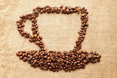 Cup of coffee from corns on fabric texture background — Stock Photo