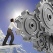 Business man pushing a cogwheel to make it work — Foto de Stock