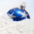 One blue christmas bauble in the snow — Stock Photo