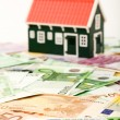 House on money field or foundation - Stock Photo