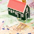 Miniature house on euro banknotes field — Stock Photo