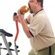 Man eating a large hamburger instead of working out — Stock Photo