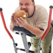 Man eating huge hamburger on a trainer device — Stok fotoğraf
