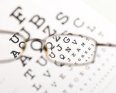 Blurry text clearing up through eyeglass — Stock Photo