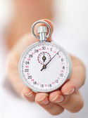 Stopwatch in womans hand - closeup — Stock Photo
