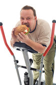 Man eating huge hamburger on a trainer device — Stock Photo
