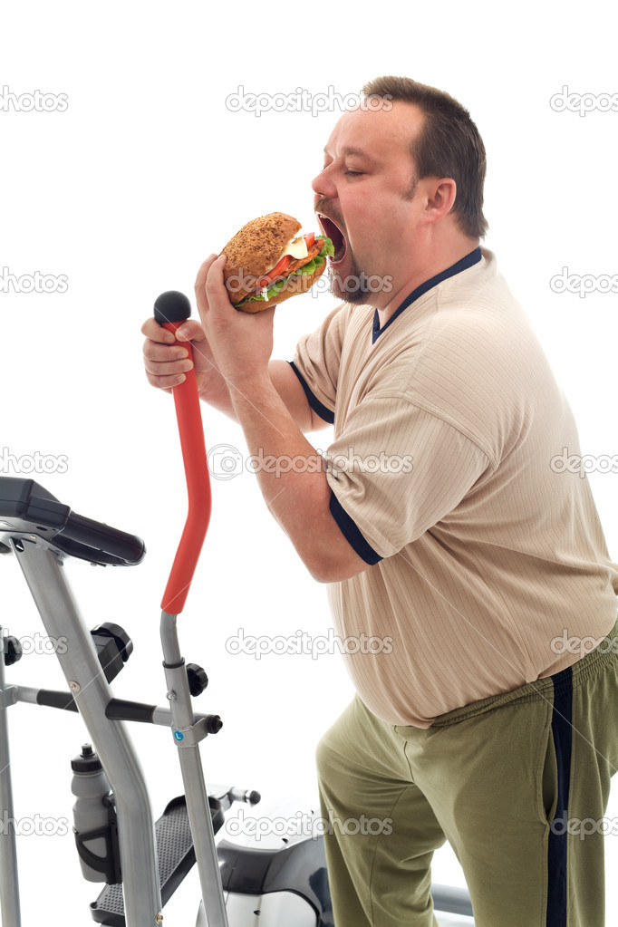 Man with gymnastic trainer device eating a large hamburger - isolated  Stock Photo #6409515