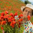 Senior woman on poppy field with a bunch of flowers — Stock Photo