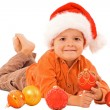 Boy in santa hat laying among christmas baubles - isolated — Stock Photo #6410433