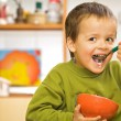 Foto Stock: Happy boy eating breakfast - cereals and milk