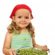 Little girl with lots of peas — Stock Photo