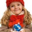Little girl in warm clothes holding blue christmas ball — Stock Photo #6411151