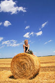 Woman sitting on a hay bale — Stock Photo