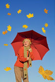 Happy woman with umbrella and falling yellow leaves — Stock Photo